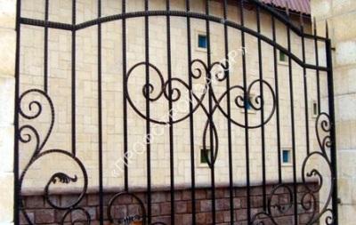 Смешанный забор с кованными элементами и кирпичными столбами